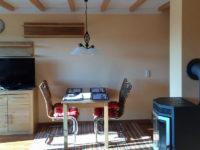 TV, Esstisch und Kamin in der Ferienwohnung Scheune